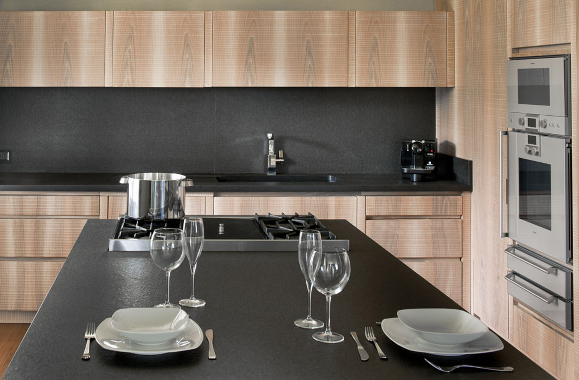 Kitchen in Italian walnut with sheer black granite surface.
